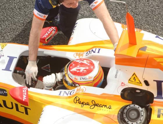 Un mecánico de Renault ayuda al monoplaza de Alonso a regresar a los boxes.  Foto: J. C. Toro
