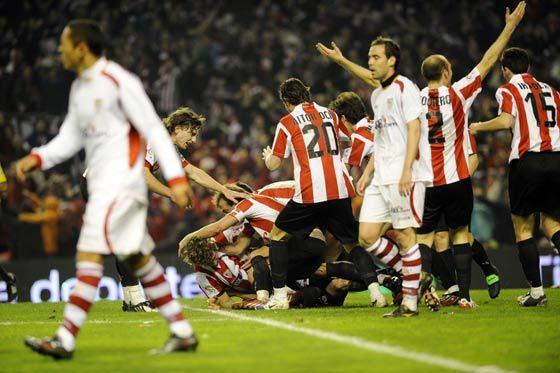 Fernando navarro y Adriano cabizbajos mientras los jugadores del Atlhetic celebran su temprano gol.  Foto: Félix Ordóñez/Agencias