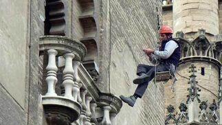 Fachada de la Giralda con un operario colgando a su lado y la Catedral de fondo.  Foto: Ruesga Bono