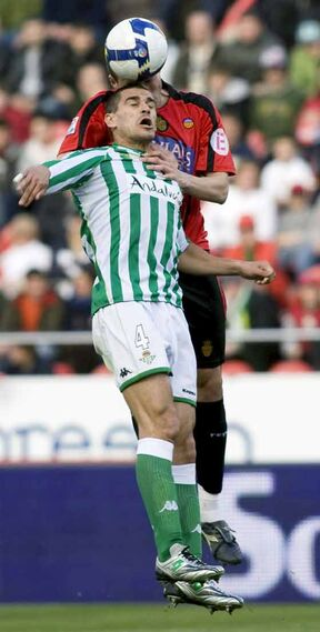 El defensa del Mallorca David Navarro disputa un balón aéreo con el defensa del Real Betis 'Juanito'.  Foto: Montserrat T. Diez (EFE)