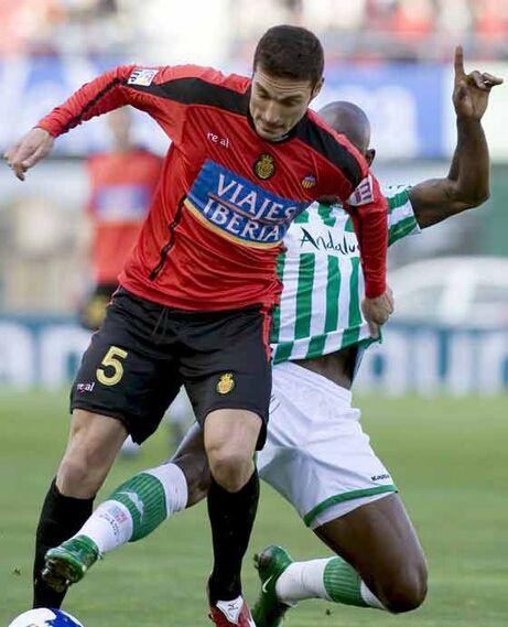 El argentino del Mallorca Lionel Scaloni disputa el balón con el centrocampista camerunés del Real Betis Achile Emaná.  Foto: Montserrat T. Diez (EFE)