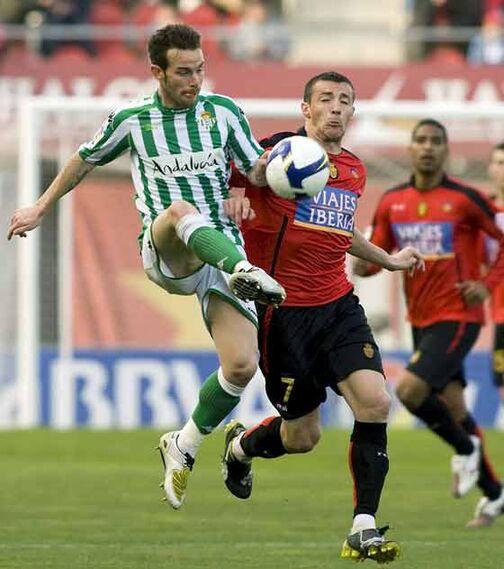 El defensa del RCD Mallorca Fernando Varela disputa el balón con el bético Fernando Vega durante el partido.  Foto: Montserrat T. Diez (EFE)