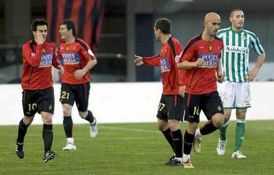Los jugadores mallorquinistas celebran uno de los goles ante la mirada de Damiá Abella.  Foto: Montserrat T. Diez (EFE)