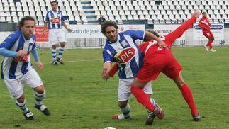 Benítez pugna con un contrario y Rafa Caro acude a la ayuda.  Foto: Vanesa Lobo