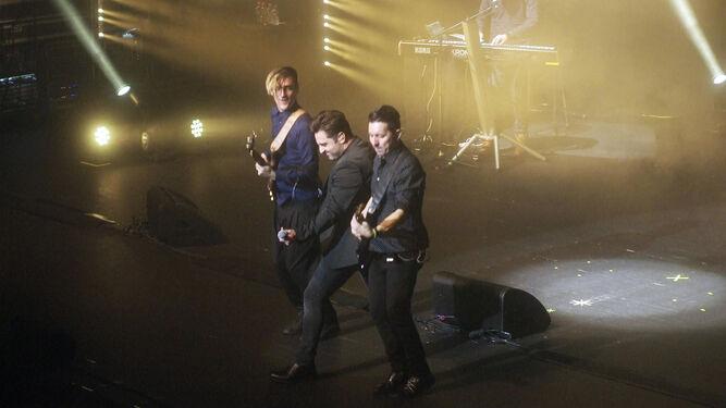 Bustamante acompañado de dos miembros de su banda al final del concierto.
