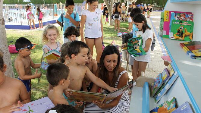 Un niño enseña ilusionado un libro a su monitora.