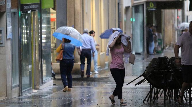 Momento más intenso de la tormenta en el Paseo de Almería, donde las terrazas de los bares tuvieron que ser recogidas rápidamente.