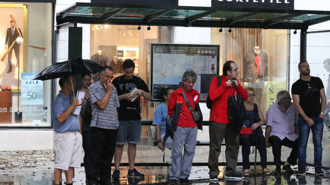La gente se refugió de la lluvia en comercios, bares y en paradas de autobús.