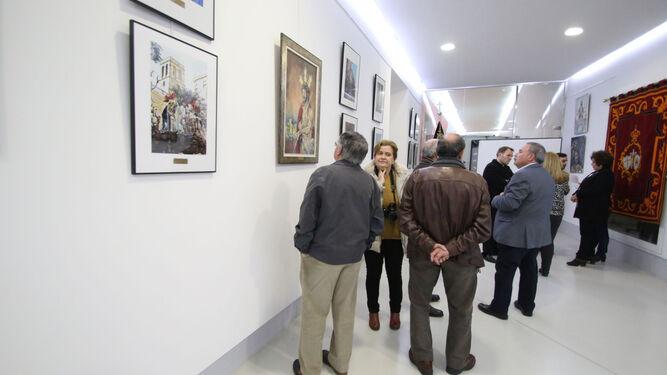 Varios cofrades visualizan los distintos trabajos de la exposición.