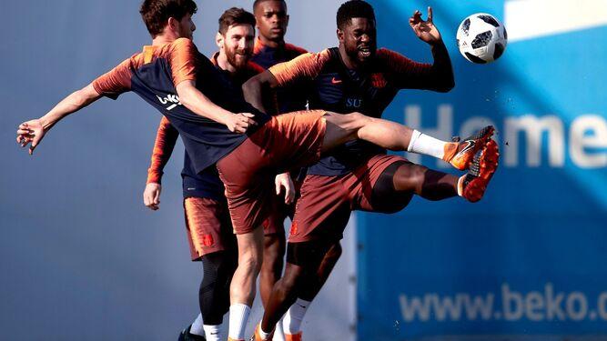 Messi sonríe, viendo a Umtiti y Sergi Roberto en el entrenamiento.