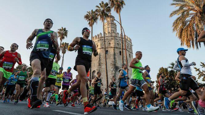Maratonianos pasando ante la Torre del Oro.